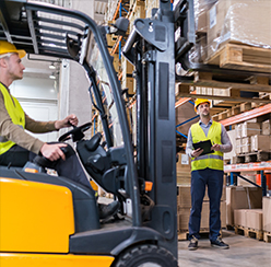 Two warehouse employees operating a fork lift to remove a pallet from a shelf