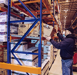 A man removing a box from an warehouse shelf