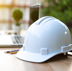 A white hard hat sitting on a table next to a laptop