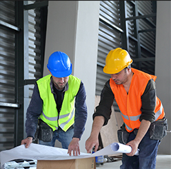 Two construction workers looking over blue prints for a build